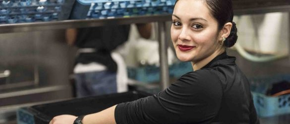 Smiling Young hispanic female kitchen worker looking at the camera